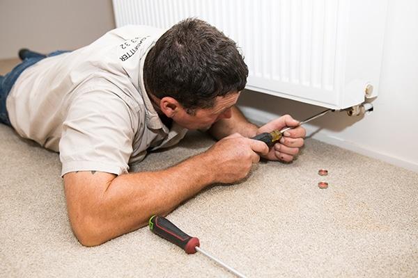plumber screwing underneath radiator